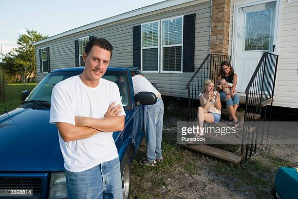 Families relaxing in front of a trailer home