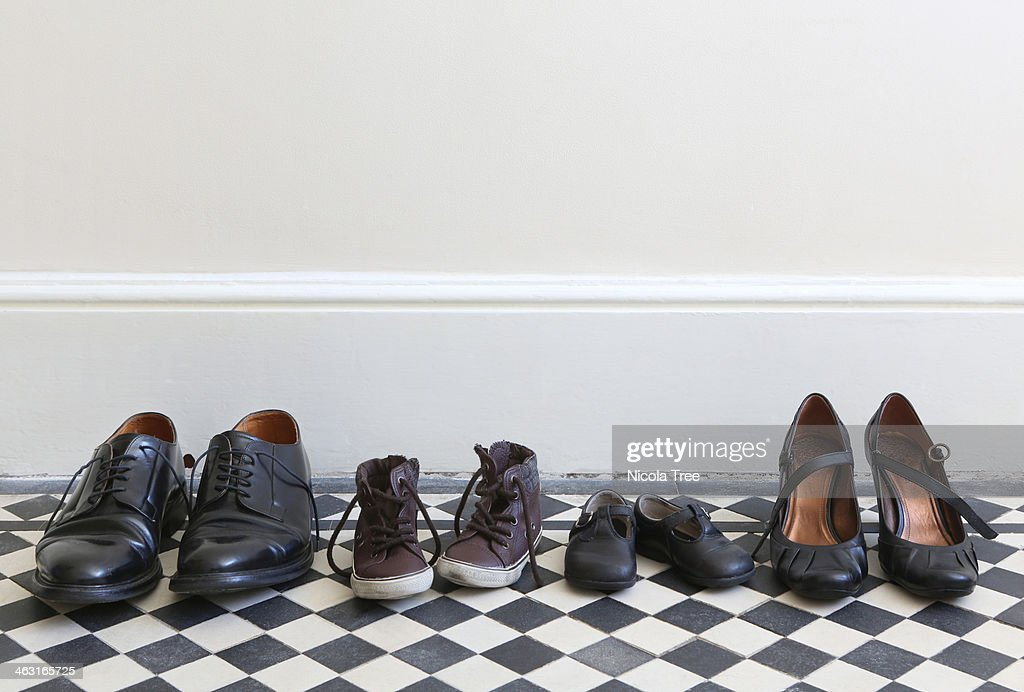 Families shoes in a row in hallway at home.