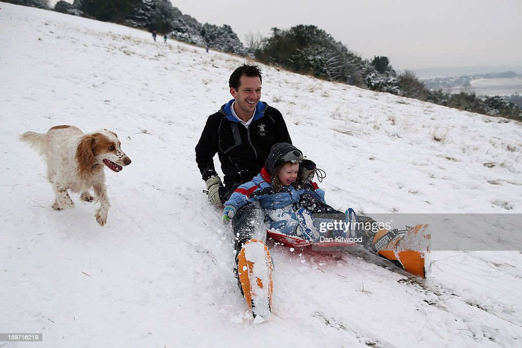 Families sledge down Box Hill on January 19, 2013 in Dorking, United Kingdom. Heavy snow around the UK caused hundreds of flight cancelations at Heathrow, with more travel disruptions expected during a snowy weekend. Approximately 3,000 schools were closed in England, Wales and Scotland.