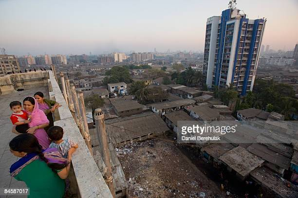 Families talk amongst themselves while they watch the sun set over the Dharavi slum as it sprawls into the distance on February 2 2009 in Mumbai...