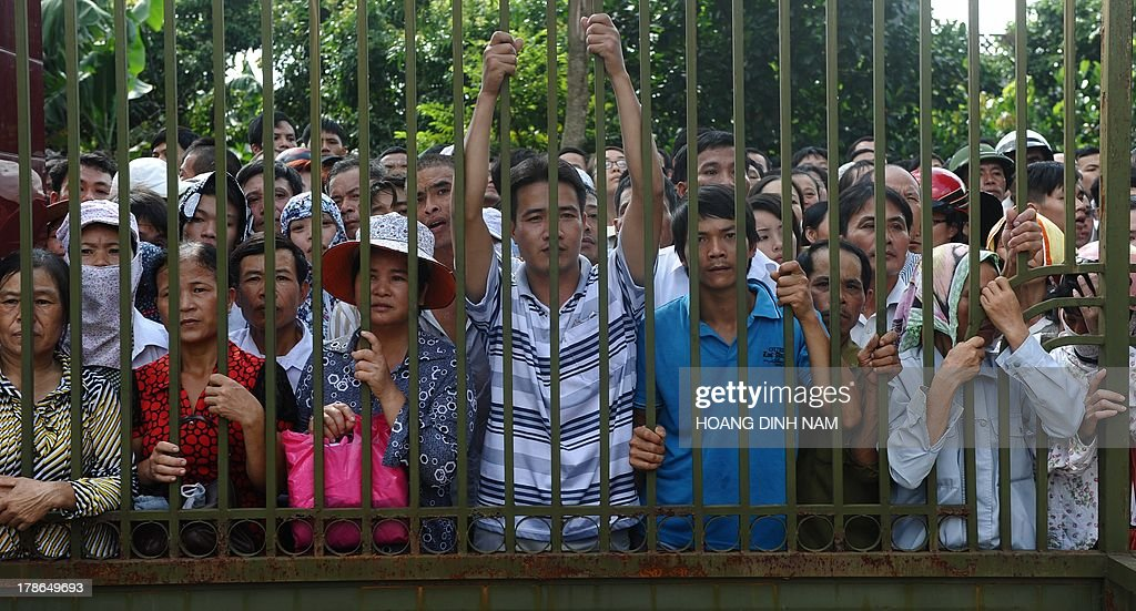 Families wait for released prisoners outside a gate at the Hoang Tien prison in Chi Linh district, northern province of Hai Duong on August 30, 2013. Vietnam will free more than 15,000 convicts to mark its independence day celebrations, the president's office said on August 29, in a major amnesty that excludes prominent political prisoners. AFP PHOTO/HOANG DINH Nam