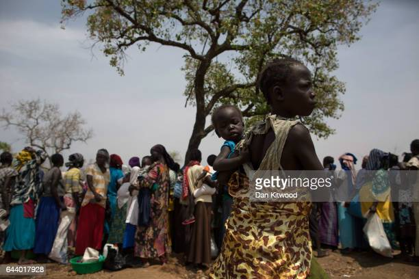 Families wait in line as WFP 'World Food Programme' prepare to deliver food aid at the Bidi Bidi refugee camp on February 22 2017 in Arua Uganda The...