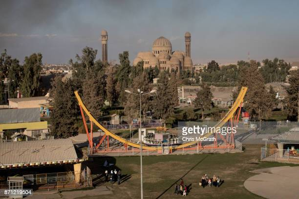 Families walk in front of a ride at the Mosul Amusement Park on November 4 2017 in Mosul Iraq The theme park was shut down under ISIS occupation and...