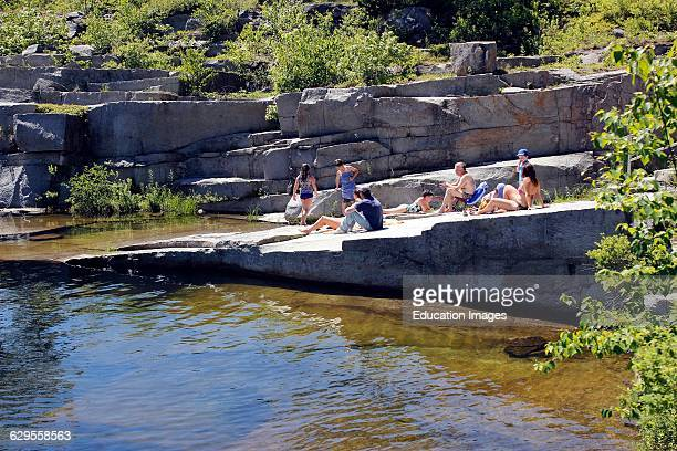 Families with children at granite quarry swimming hole Vinalhaven Island Maine New England USA