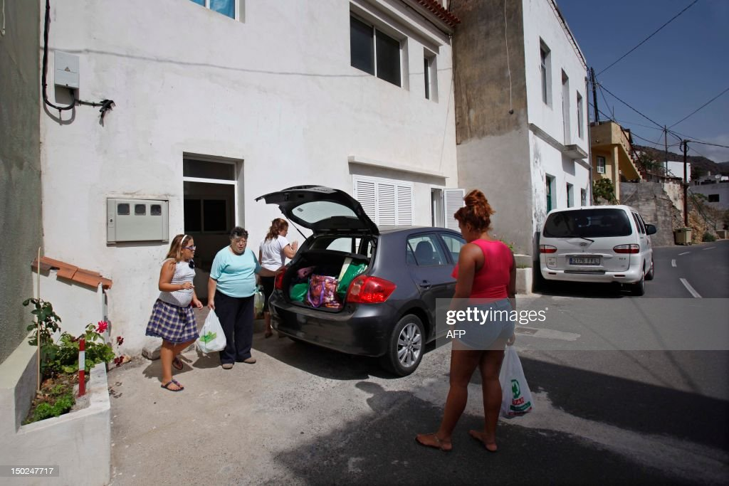 A familly gets ready for evacuation in Vallehermoso, on August 13, 2012, on the Spanish canary island of La Gomera. Wildfires killed two people in south-eastern-Spain and forced thousands to evacuate in the Canary Islands where flames ravaged a rare nature reserve, authorities said Monday.