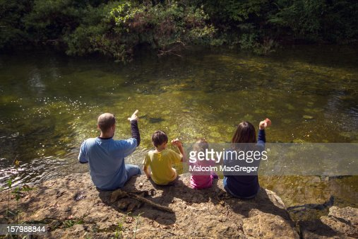 Familly of Four Throwing Rocks into River