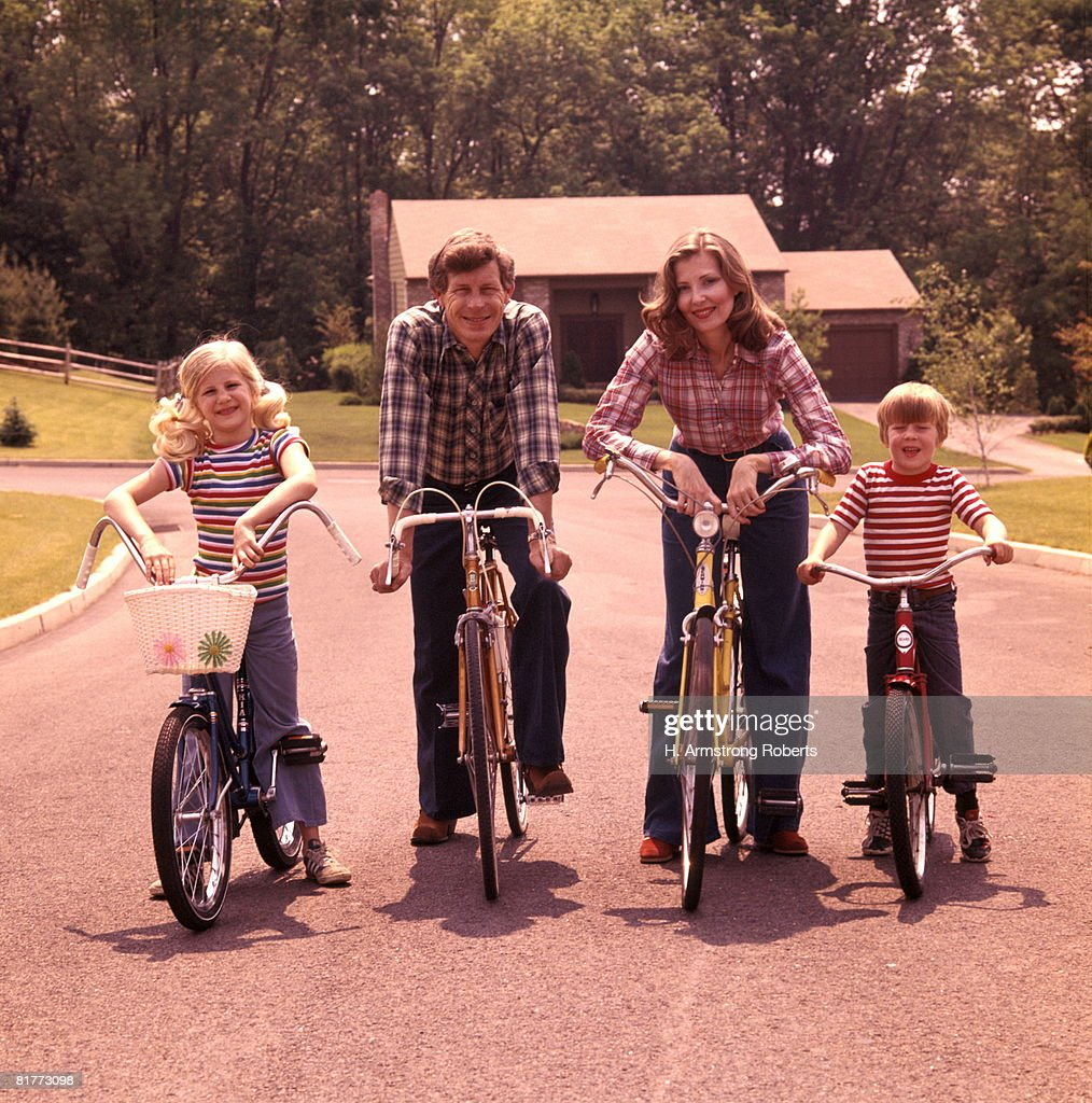 Family 4 Bicycle Portrait Mother Father Boy Girl Bikes Suburban Street House Suburbia Families Retro. : Stock Photo