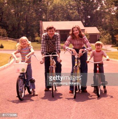 Family 4 Bicycle Portrait Mother Father Boy Girl Bikes Suburban Street House Suburbia Families Retro. : Stock Photo
