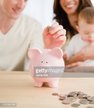 Family adding coins to piggy bank together : Stock Photo