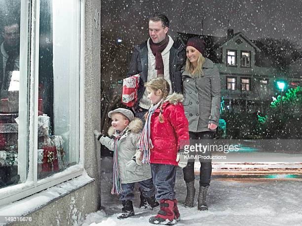 Family admiring Christmas window in snow