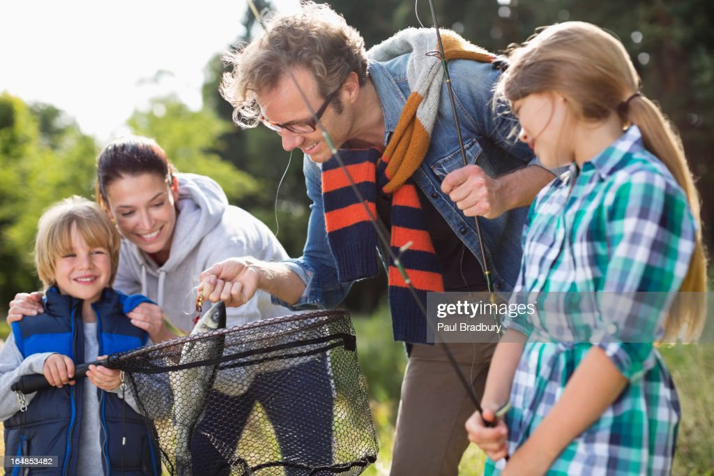 Family admiring fishing catch : Stock Photo