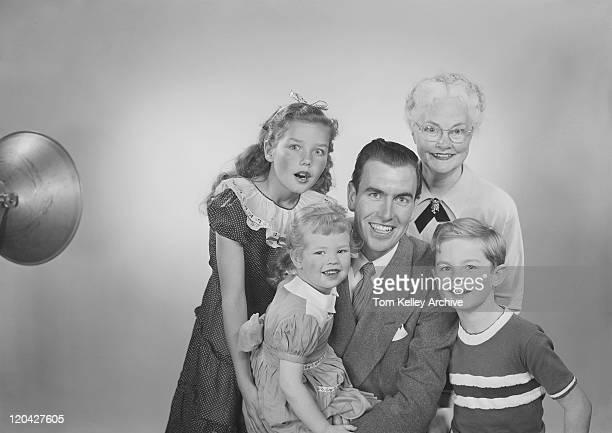Family against white background, smiling, portrait