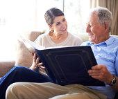 A senior man and his daughter looking at old family photos at the nursing home