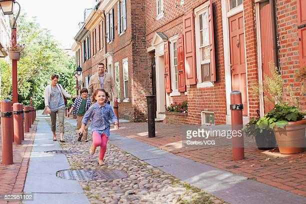 Family and daughter (6-7) running along town street, Philadelphia, Pennsylvania, USA