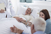 Family and doctor visiting patient in hospital