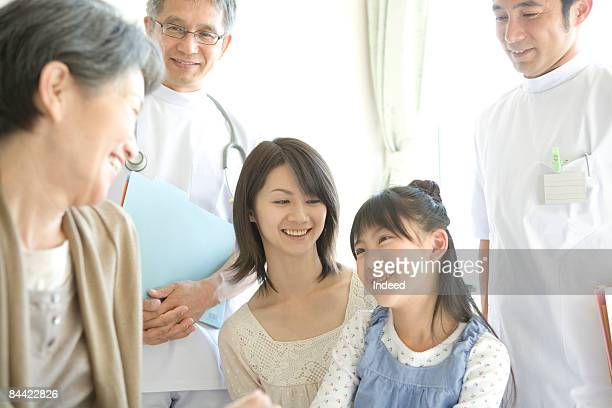 Family and doctors visiting mid adult woman by bed
