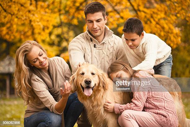 Family and dog enjoying autumn day in the park