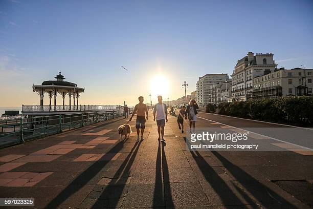 Family and dog walking along seafront prom