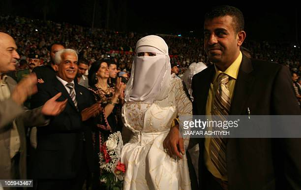 Family and friends clap as a Palestinian couple walk past during a mass wedding in the northern West Bank city of Nablus as 49 Muslim couples tie the...