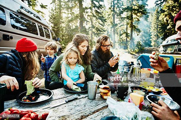 Family and friends eating breakfast while camping