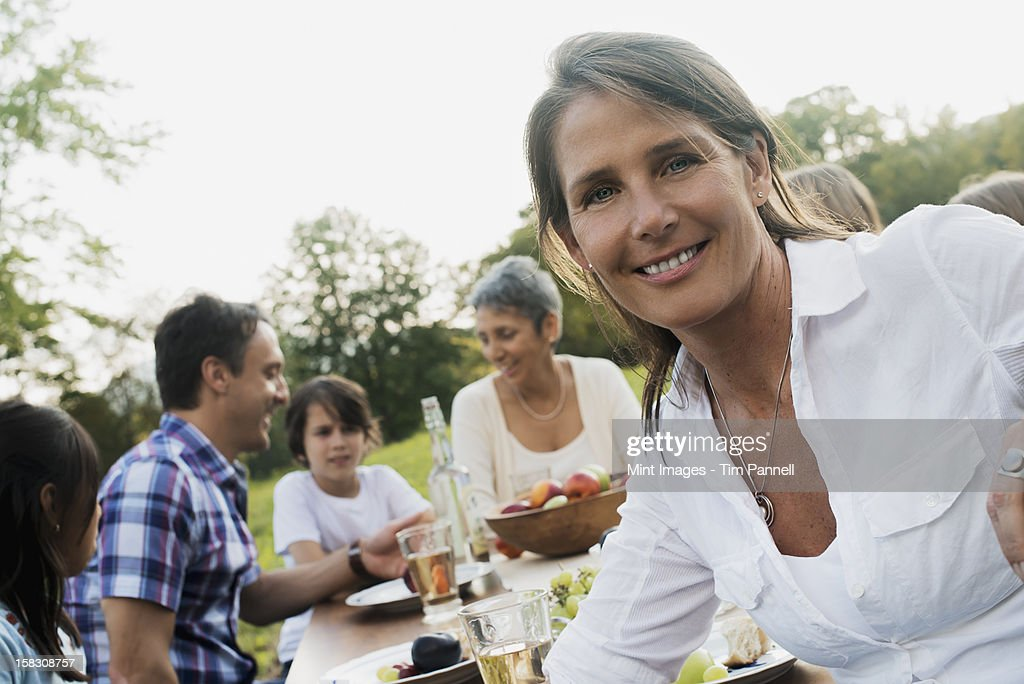 A family and friends having a meal outdoors.  A picnic or buffet in the early evening. : Stock Photo