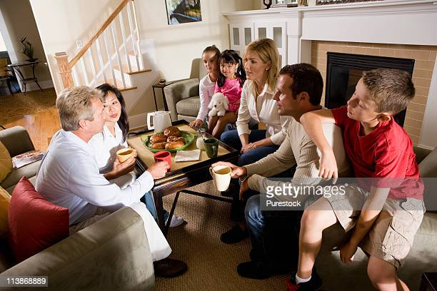 Family and friends having breakfast together in living room