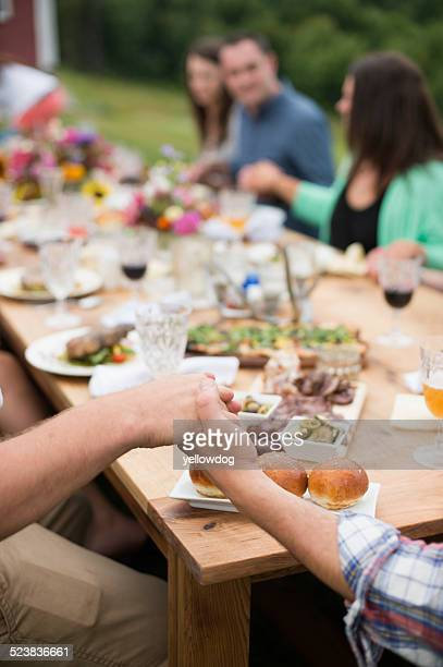 Family and friends holding hands around dinner table, outdoors