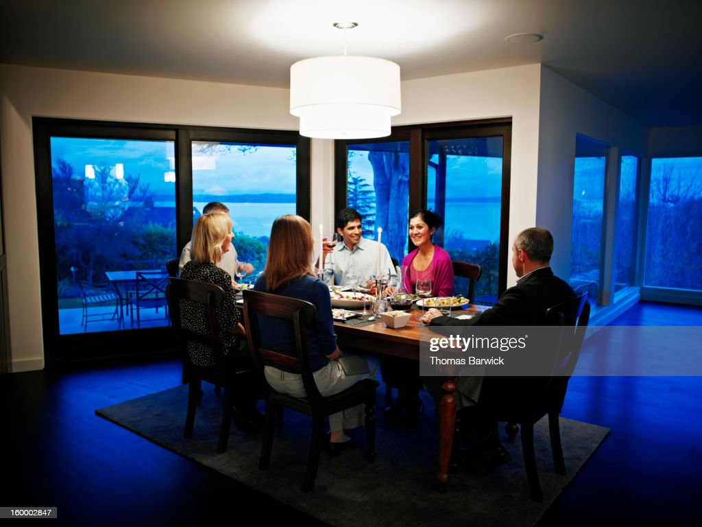 Family and friends in dinning room eating dinner : Stock Photo