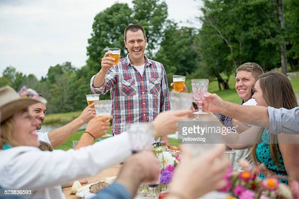 Family and friends making a toast at outdoor meal