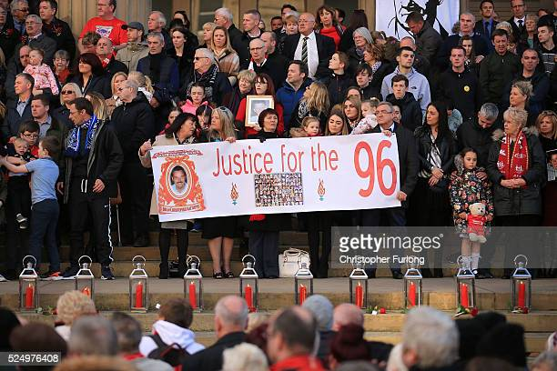 Family and friends of the victims hold up a banner on the steps outside Liverpool's Saint George's Hall as thousands of people gather to attend a...