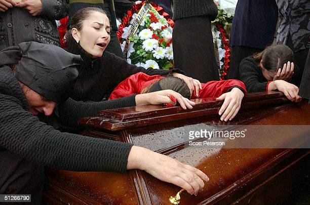 Family and friends of those killed in the school hostage crisis cry over the coffin of a loved one during a mass funeral in the rain September 6 2004...