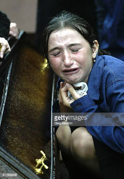 Family and friends of those killed in the school hostage crisis cry during a mass funeral in the rain September 6 2004 in Beslan southern Russia More...