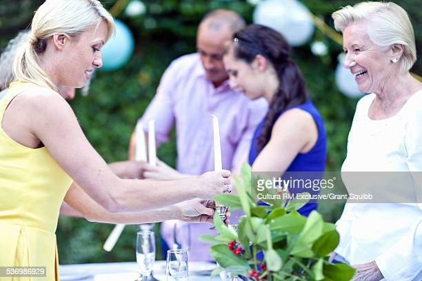 Family and friends preparing garden party table