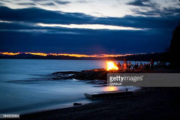 Famille et amis, assis autour de feu de camp au coucher du soleil