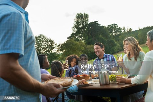 A family and friends sitting at a table outdoors having a meal. : Stockfoto