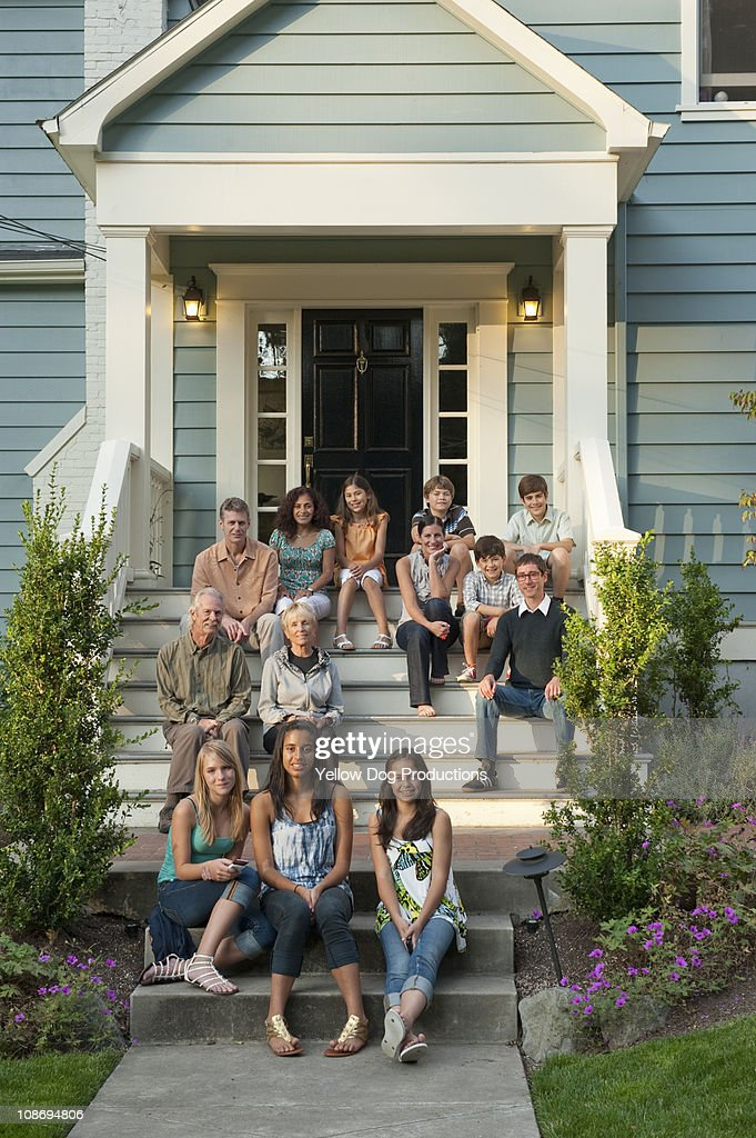 Family and Friends sitting on front steps of house : Stock Photo