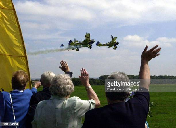 Family and friends wave at highflying couple Caroline Hackwood and Justin Bunn during their airborne wedding ceremony strapped to the wings of 1940s...