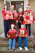 Family and grandparents holding Christmas presents in front of home