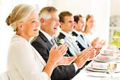 Family And Guests Clapping At Table During Reception