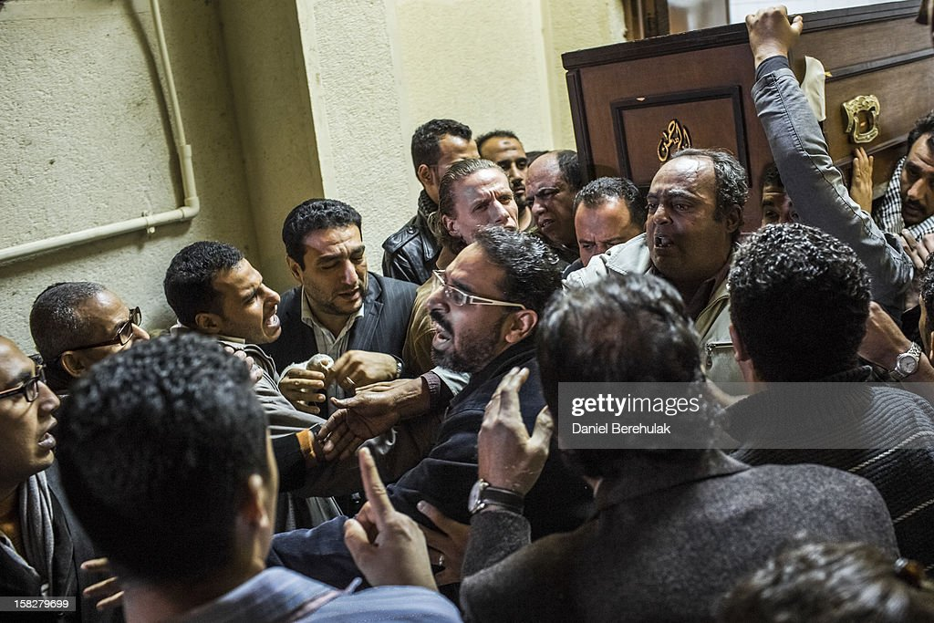 Family and loved ones of killed journalist El-Hosseiny Abou-Deif mourn as his body is carried from a morgue on December 12, 2012 in Cairo, Egypt. Egyptian journalist El-Hosseiny Abou-Deif who was hit in the head with a rubber bullet in last week's clashes at the presidential palace, was announced dead on Wednesday after spending a week in a coma. Anti-Morsi protesters were quiet after continued demonstrations across Egypt against the country's draft constitution, rushed through parliament in an overnight session on November 29. The country's new draft constitution, passed by a constitutional assembly dominated by Islamists, will go to a referendum on December 15.