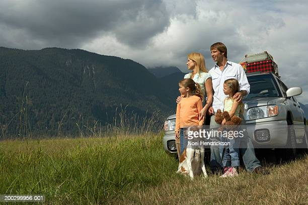 Family and pet spaniel standing beside car, looking at rural scenery