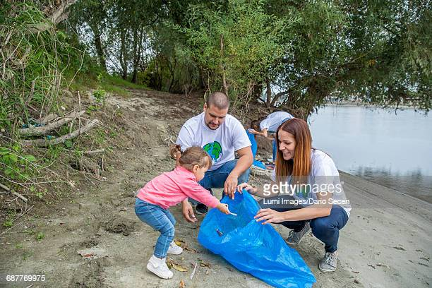 Family and volunteers doing garbage cleanup in park