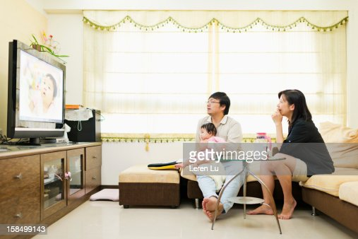 Family are looking at TV in living room : Stock Photo