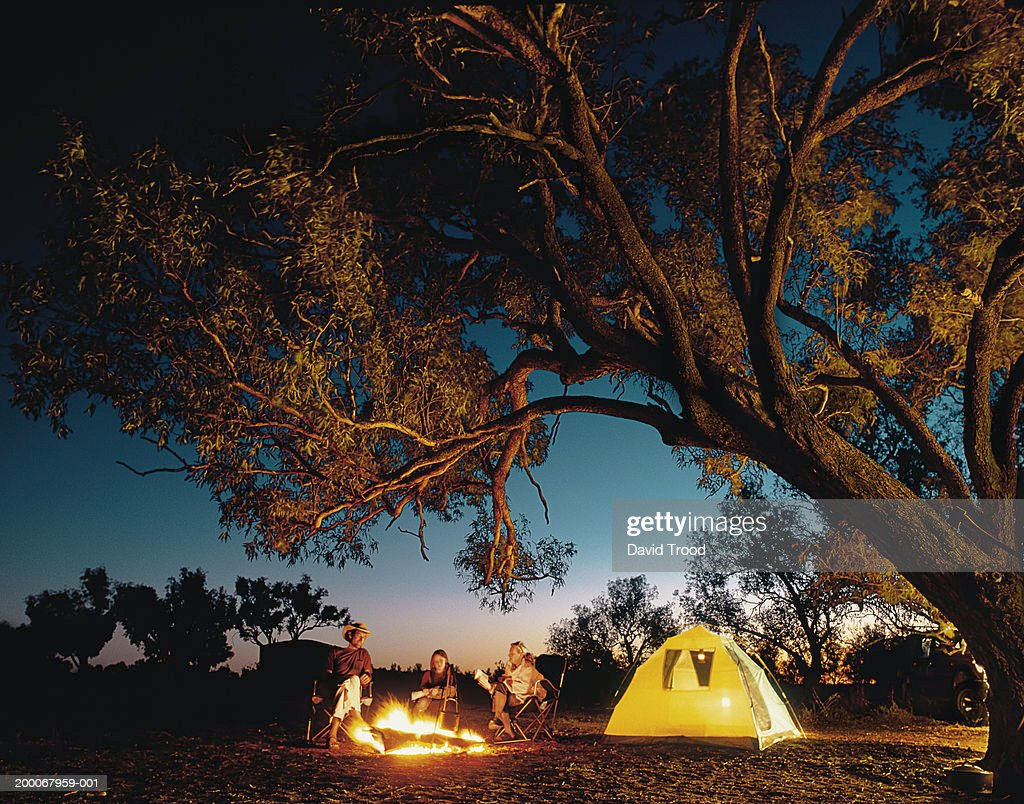 Family around camp fire, night (Digital Composite) : Stock Photo