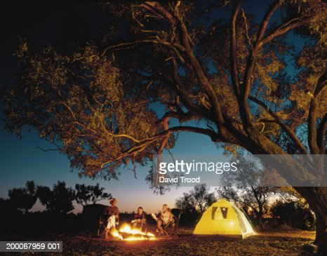 Family around camp fire, night (Digital Composite) : Stock Photo