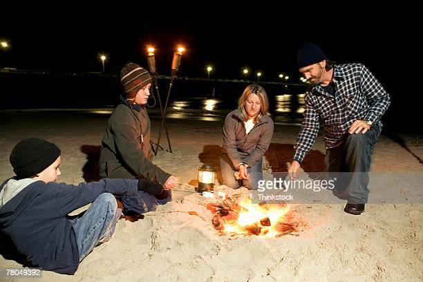 Family around campfire on beach