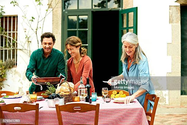 Family arranging outdoor meal table