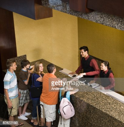 Family arrive at hotel and greeted by hotel staff : Stock Photo