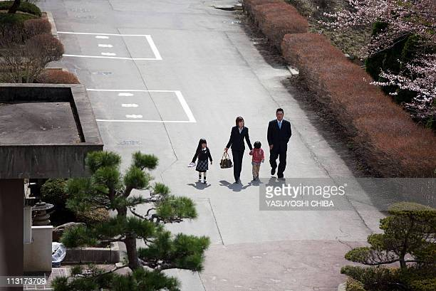 A family arrives to attend the entrance ceremony for Funakoshi elementary school at the Ishinomakikita highschool in Ishinomaki Miyagi prefecture on...