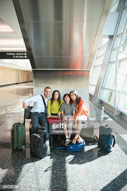 family at airport looking at camera